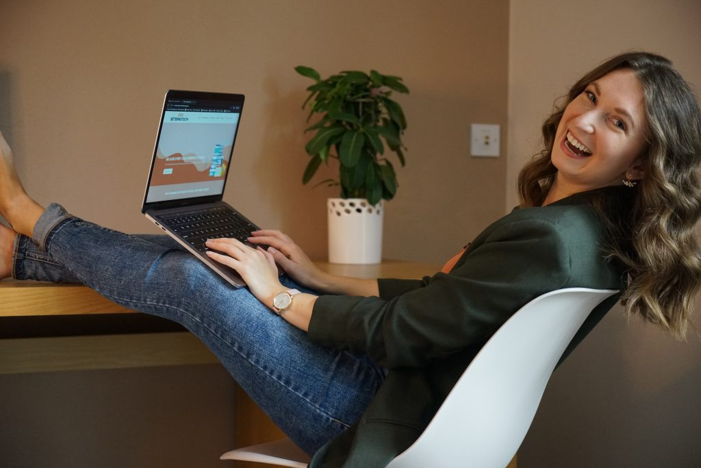 Sarahlynn Hodder sitting at a desk with her laptop open to Bettering Youth website